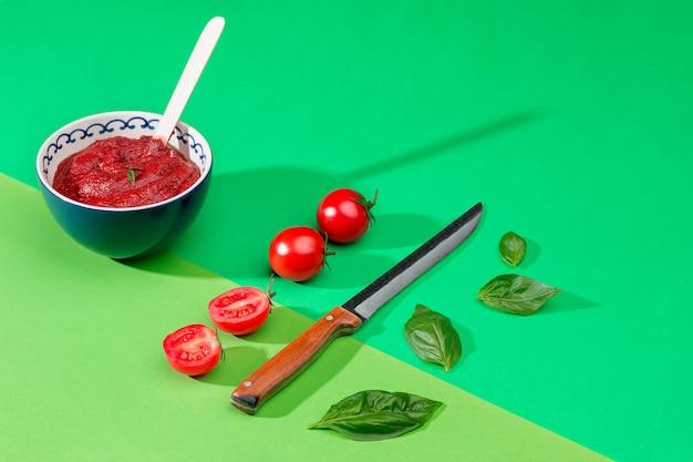 緑のテーブルに刻んだトマトのボウル