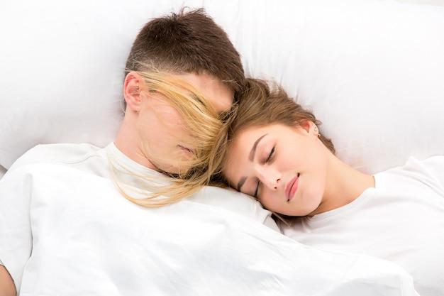 ベッドに横たわって若い素敵なカップル