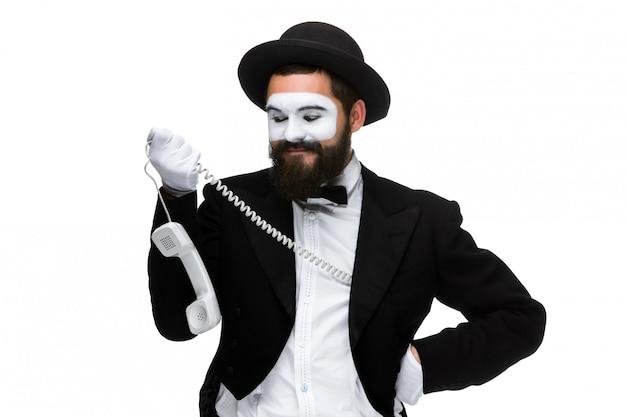 Человек в изображении пантомимы, держащем телефонную трубку.