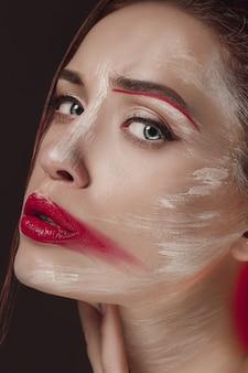 色の顔を持つファッションモデルの女性が描かれています。カラフルな抽象的なメイクと美しい女性の美容ファッションアートの肖像画。