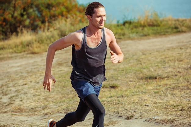Бег спорт. бегущий человек спринте открытый в живописной природе. приспособьте мускулистую мужскую спортивную тренировочную тропу, бегущую для пробега марафона
