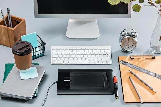 Серый письменный стол с ноутбуком, блокнотом с чистым листом, горшком с цветком, стилусом и планшетом для ретуши