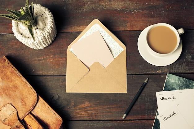 クラフト紙の封筒、紅葉、木製のテーブルの上のコーヒーを開く