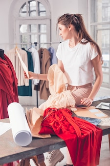 机の上に座っているスタジオで働くファッションデザイナーの女性