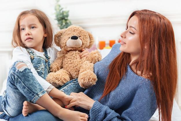 Маленькая милая девушка наслаждается, играет и создает с игрушкой с матерью