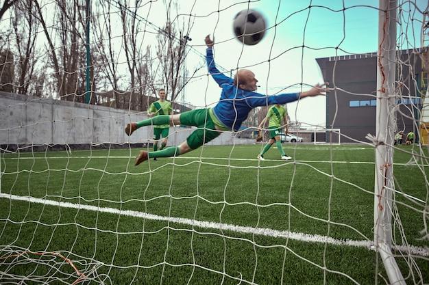 サッカーサッカーのゴールキーパーがダイビングを保存する