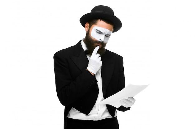 紙のリストを読むビジネスマンとして物思いに沈んだパントマイム
