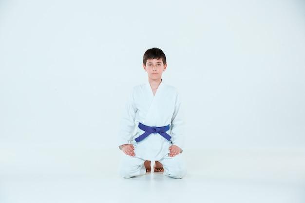 Мальчик позирует на айкидо на тренировке в школе боевых искусств. концепция здорового образа жизни и спорта