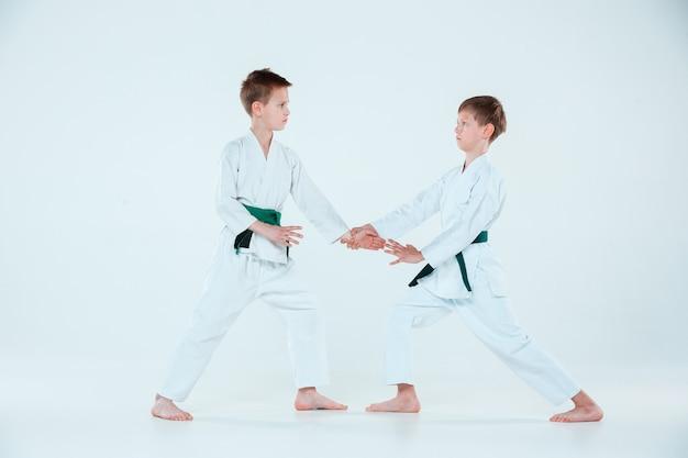Два мальчика воюют в айкидо на тренировке в школе боевых искусств. концепция здорового образа жизни и спорта