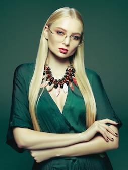 エレガントな緑のドレスで金髪の若い女性。