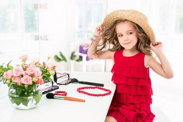 鏡の近くに座っている化粧品を持つ少女。