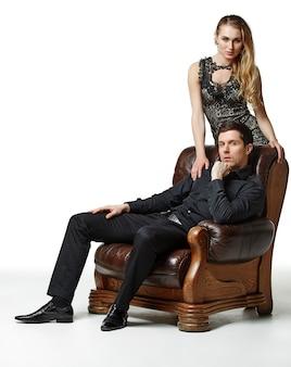 Мода мужчина и женщина на винтажном кресле