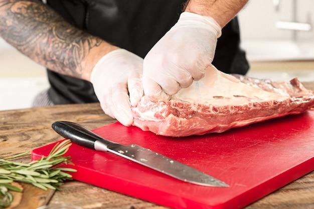 キッチンで肉ステーキを調理する男