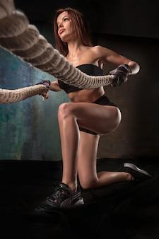 ジムでロープを引っ張る強い若い女性