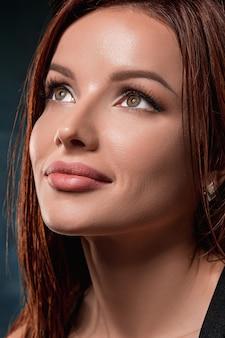 Красивый портрет лица женщины крупным планом на темноте