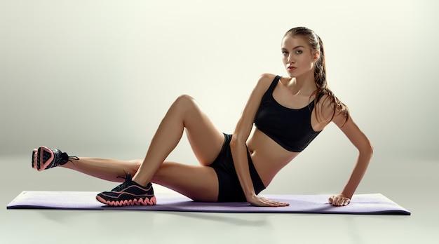 魅力的な女性は、ライラックマットにフィットネス運動を行う