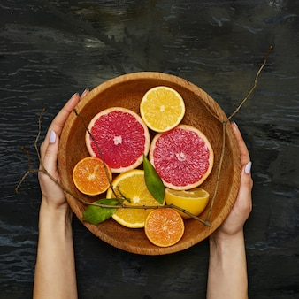 Половинки цитрусовых фруктов грейпфрута на деревянной тарелке