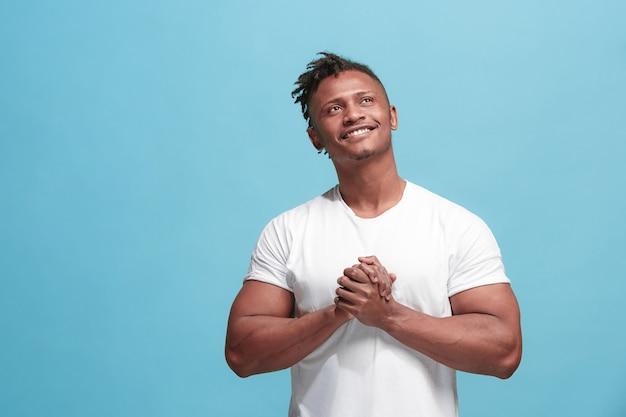 幸せなビジネスのアフリカ系アメリカ人の男に立っていると青に対して笑みを浮かべて