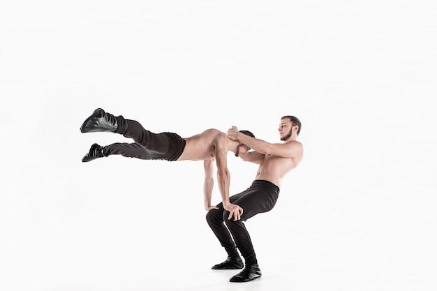 Группа гимнастических акробатических кавказских мужчин на позе равновесия