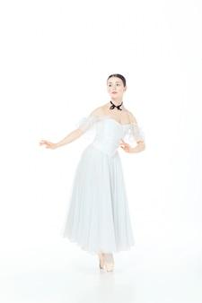 トウシューズでポーズをとって白いドレスのバレリーナ