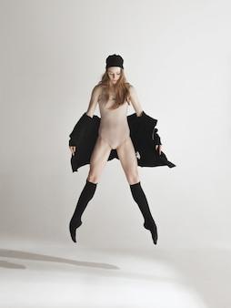 ベージュ水着ダンスの若い美しいダンサー