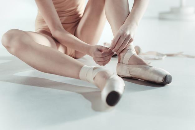 Красивая маленькая балерина надевает пуанты
