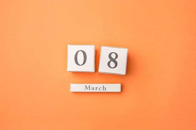 木製カレンダーとオレンジ色のテーブル