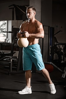 ジムで体重の演習を行う筋肉ボディービルダー男