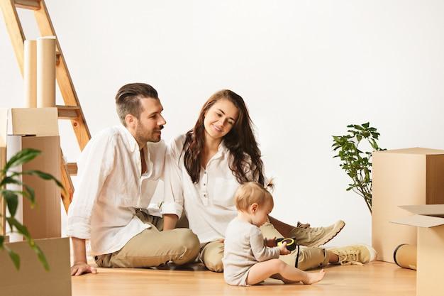 新しい家に移動するカップル。幸せな既婚者が新しいアパートを購入して一緒に新しい生活を始めます