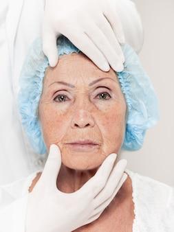 整形外科の前に中年の女性の皮膚チェックを行う外科医