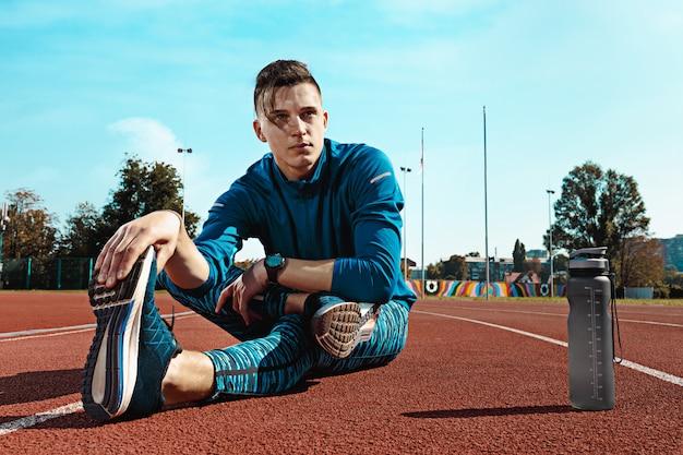 Бегущий человек разминает ноги, готовится к бегу на стадионе, делает разминку