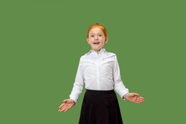 緑に分離されて驚いて見ている美しい十代の少女