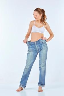 女性はスキニーになり、古いジーンズを着て