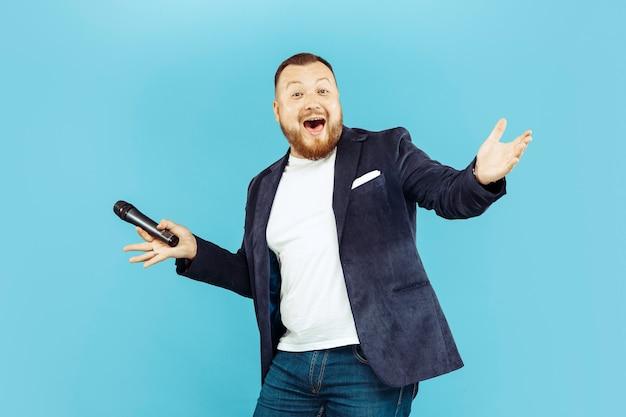 Молодой человек с микрофоном на синем, ведущей концепции