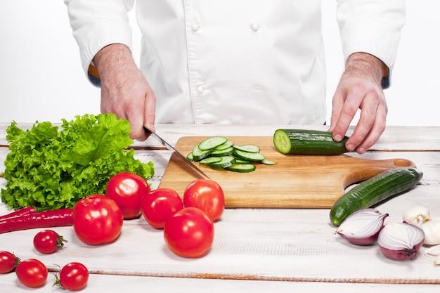 彼のキッチンで緑のキュウリを切るシェフ