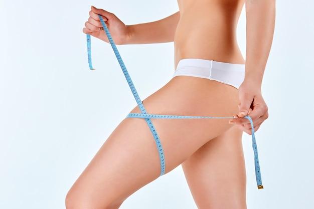 Женщина держит метр измерения идеальной формы ее красивого тела