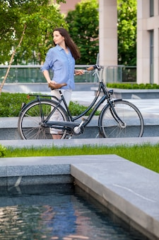 Красивая девушка с велосипедом на дороге