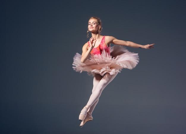 灰色の背景に美しい女性バレエダンサー。バレリーナはピンクのチュチュとポアントシューズを履いています。