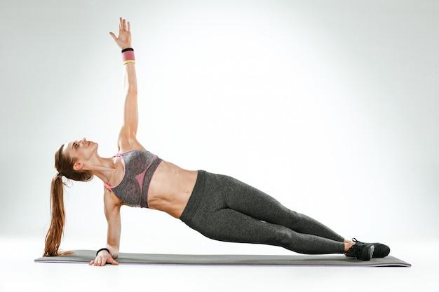 Красивая стройная брюнетка делает упражнения на растяжку в тренажерном зале
