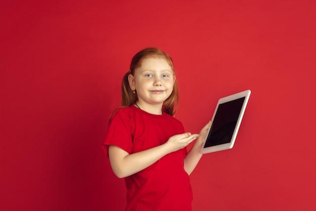 Кавказская маленькая девочка с цифровым планшетом