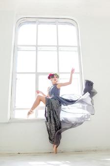 Красивая балерина позирует в длинном сером платье
