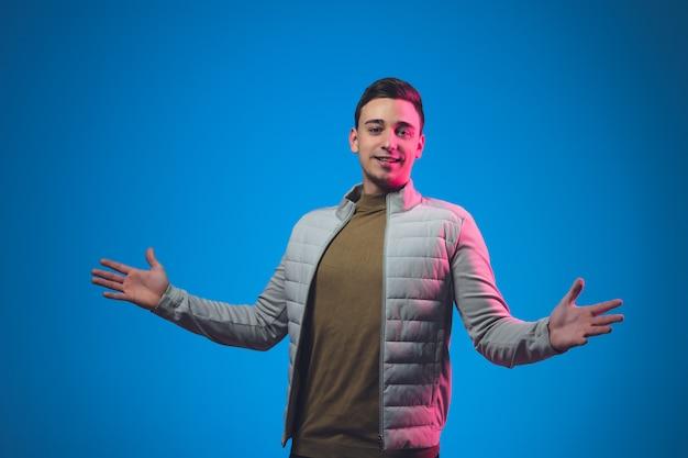 Закройте вверх по портрету кавказского человека изолированному на голубой студии в неоновом свете
