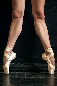 黒い木製の床にクローズアップバレリーナの脚と拍