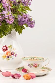 レモンとテーブルの上のライラックサクラソウの花束とお茶