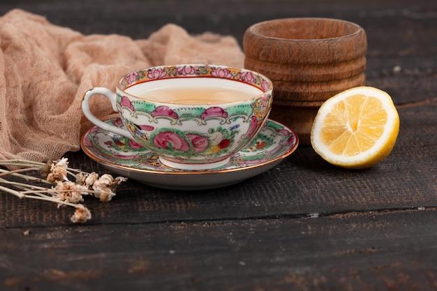 テーブルの上のレモンとサクラソウのお茶