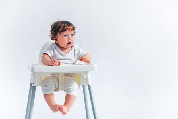 Счастливый ребёнок сидя на стуле младенца