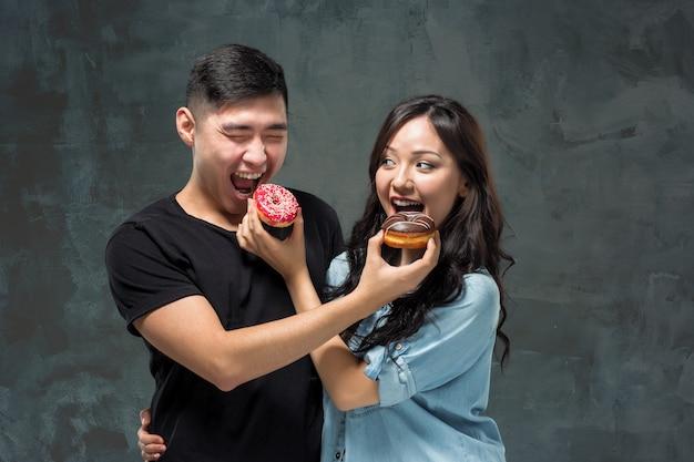 若いアジアのカップルは、甘いカラフルなドーナツを食べてお楽しみください