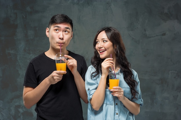 オレンジジュースのグラスを持つ若いかなりアジアカップル