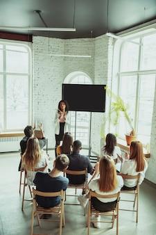Женский афроамериканец оратор дает представление в зале на семинаре университета