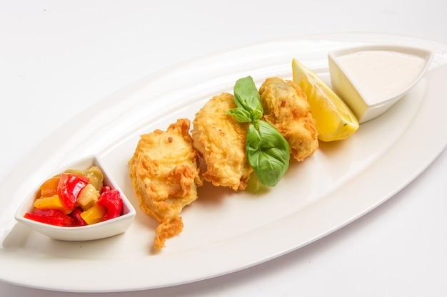 ソース、レモン、野菜の衣で揚げた魚のフライ